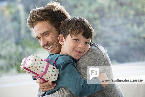 Liebevolle Umarmung von Vater und Sohn mit Geburtstagsgeschenk