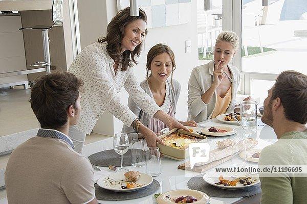 Eine glückliche reife Frau  die ihren Freunden Essen serviert.