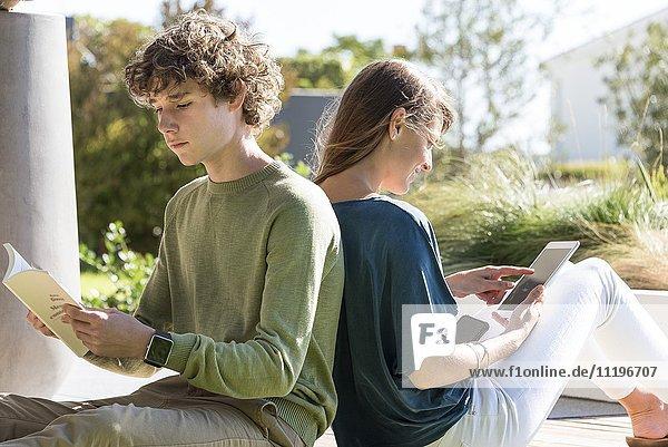 Bruder und Schwester sitzen Rücken an Rücken mit Buch und Tafel im Garten