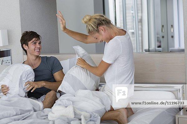 Glückliches Paar mit Kissenschlacht auf dem Bett