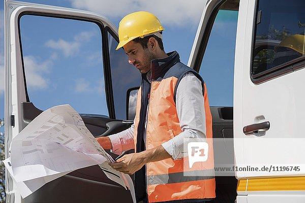 Männlicher Ingenieur beim Lesen eines Bauplans vor Ort