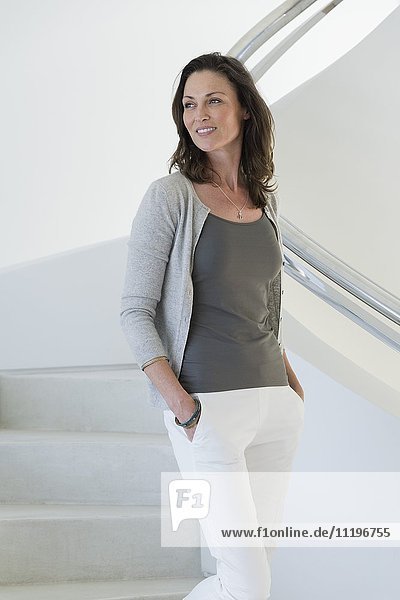 Glückliche schöne Frau auf der Treppe stehend