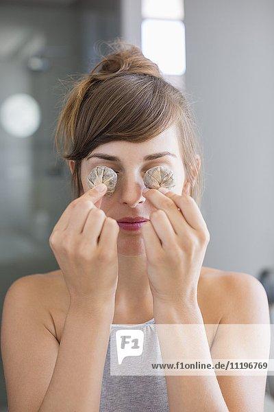 Schöne Frau hält Teebeutel vor ihren Augen