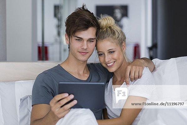 Ein junges Paar  das einen Selfie auf dem Bett nimmt.