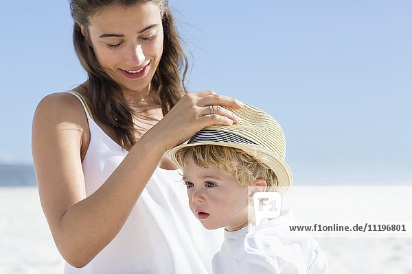 Frau  die einen Hut auf ihren Babykopf setzt.