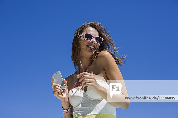 Beautiful woman listening music with mobile phone
