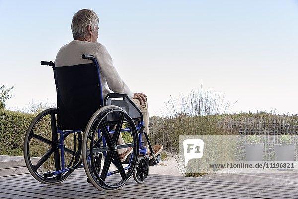 Senior im Rollstuhl entspannt im Freien