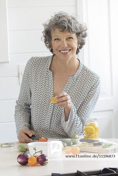Glückliche Frau beim Zubereiten von Speisen in der Küche