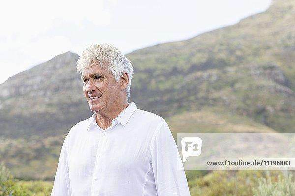 Glücklicher älterer Mann genießt in einem Tal