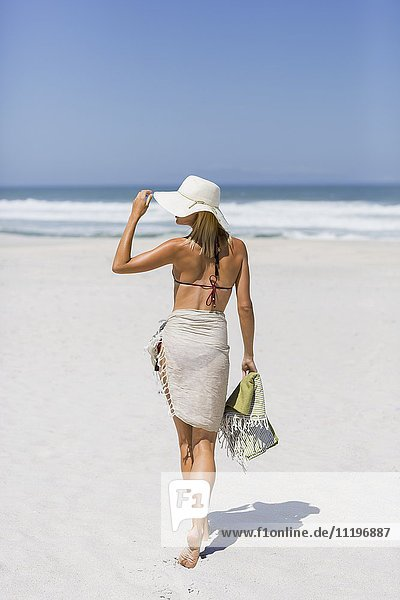 Rückansicht einer schönen Frau beim Spaziergang am Strand