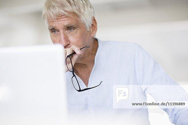 Serious Senior Mann Blick auf Laptop auf dem Tisch