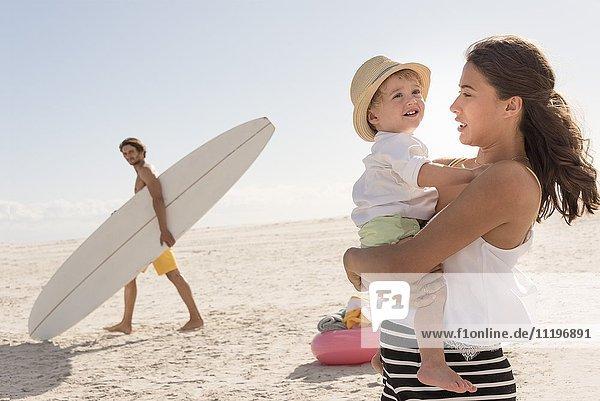 Glückliche junge Familie genießt am Strand