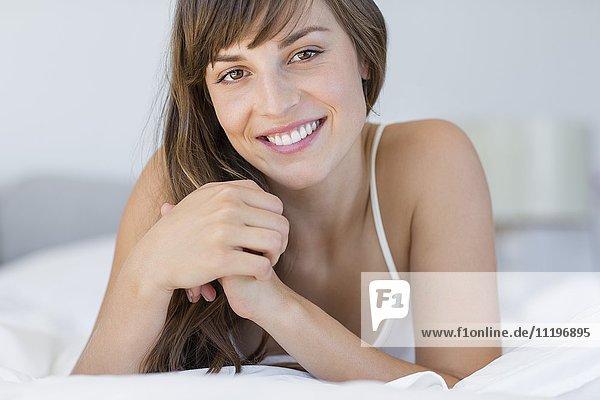 Schöne junge Frau  die sich auf dem Bett entspannt.
