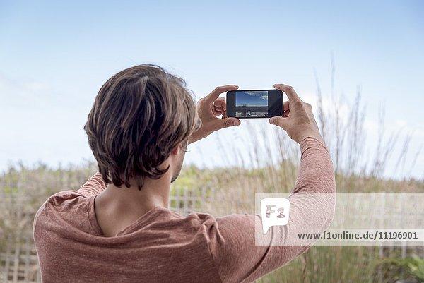 Junger Mann beim Fotografieren mit Fotohandy