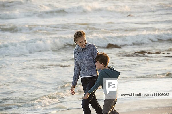Happy mother and son walking on the beach