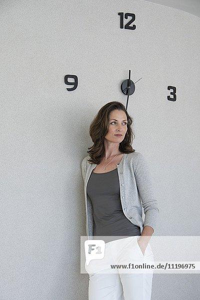 Schöne Frau  die sich an eine Wand lehnt und denkt.