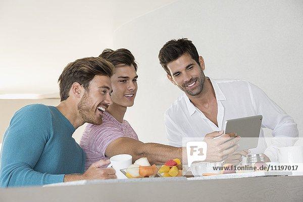 Glückliche männliche Freunde  die Selfie mit Tablette auf dem Frühstückstisch zu Hause einnehmen