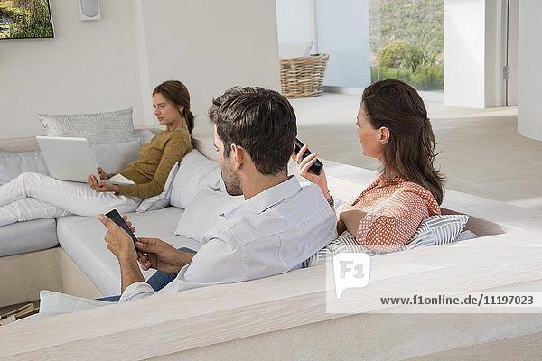 Dreiköpfige Familie im Wohnzimmer mit verschiedenen Aktivitäten