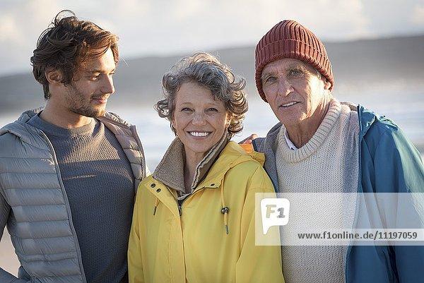 Porträt einer glücklichen Familie am Strand stehend