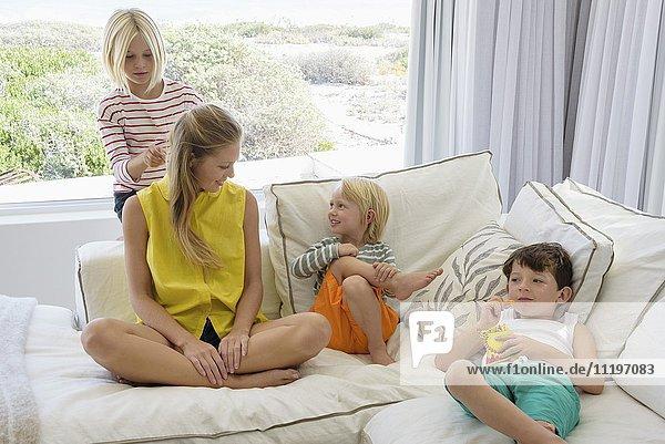Glückliche Mutter und Kinder sitzen auf der Couch im Wohnzimmer