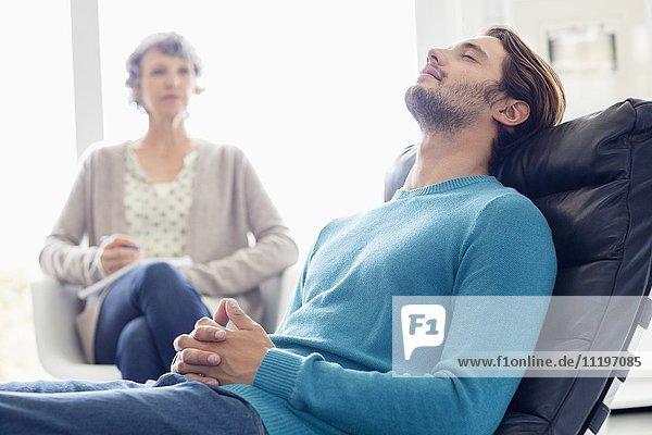 Ernsthafte Mutter und Sohn sitzen zusammen im Wohnzimmer