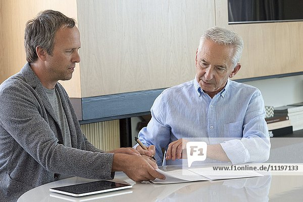 Senior man doing paperwork with financial advisor at home