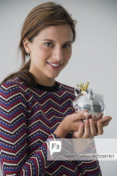 Porträt einer glücklichen Frau mit einem Sparschwein