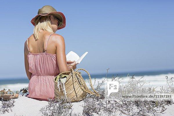 Schöne Frau  die ein Buch am Strand liest.