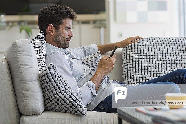 Mann  der auf einer Couch sitzt und ein Smartphone benutzt.