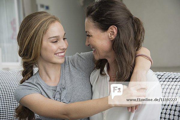 Mutter und Tochter lächeln sich an.