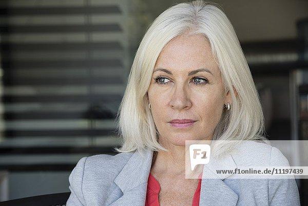 Reife Geschäftsfrau denkt im Büro