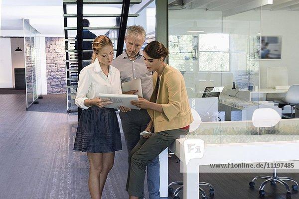Geschäftsleute  die eine Zeitschrift in einem Büro anschauen.