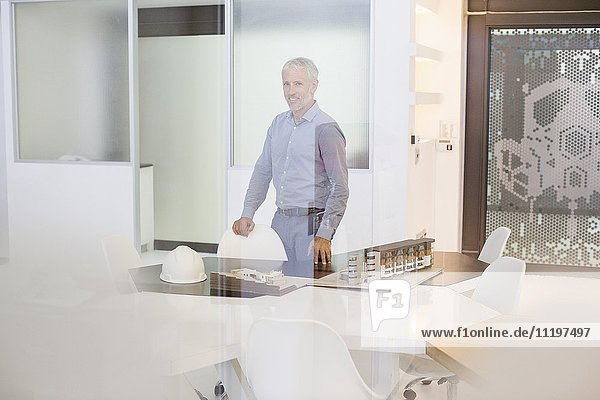 Design professional with architectural model in an office