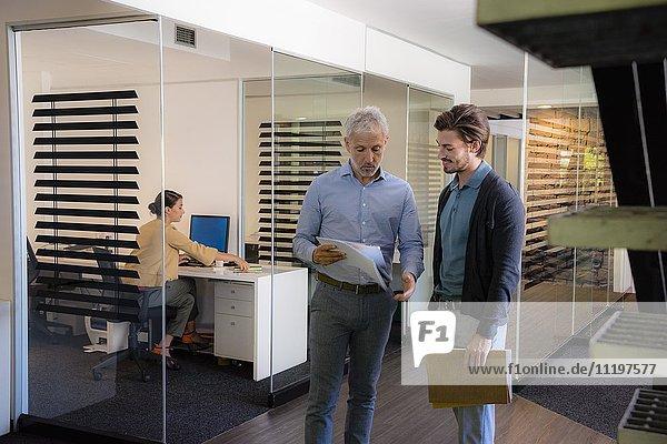 Zwei Geschäftsleute betrachten eine Akte mit einer Geschäftsfrau  die im Hintergrund arbeitet.