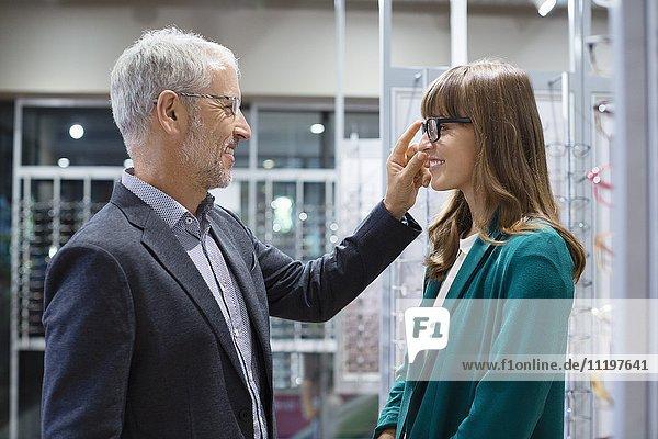 Verkäuferin hilft dem Kunden beim Anprobieren der Brille im Optikgeschäft