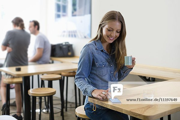 Happy woman drinking coffee and using a smart phone in a restaurant