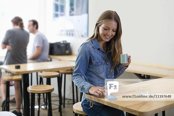 Glückliche Frau trinkt Kaffee und benutzt ein Smartphone in einem Restaurant.