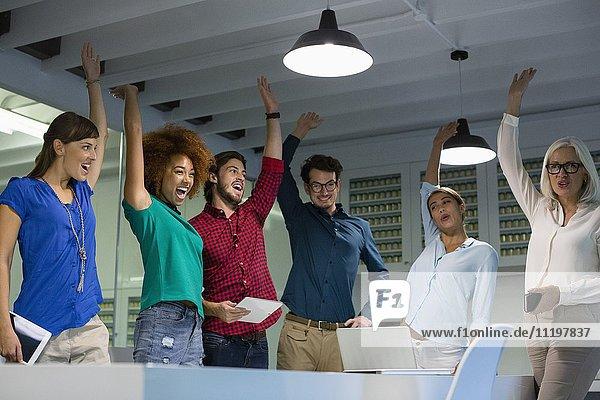 Happy business people cheering in meeting