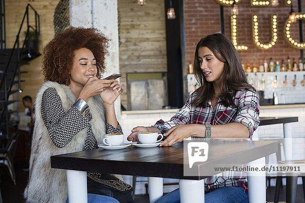 Freundinnen beim Fotografieren einer Kaffeetasse mit Smartphone im Café