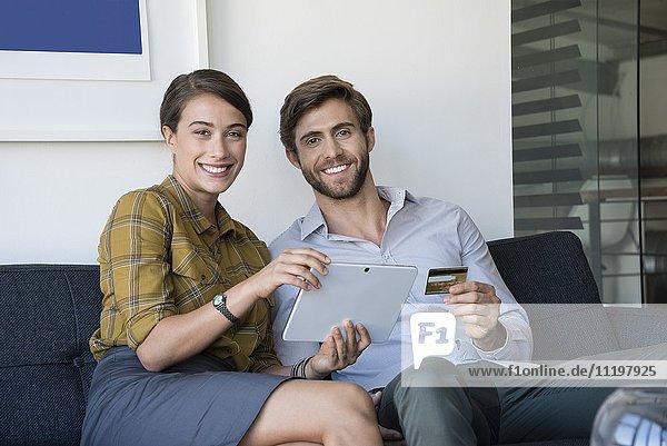 Glückliches Paar beim Online-Shopping auf dem digitalen Tablett