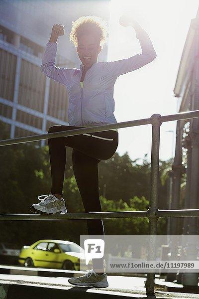 Fröhliche junge Sportlerin beim Stretching am Geländer auf der Straße