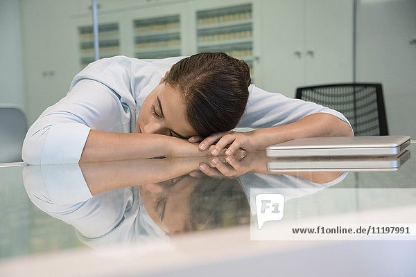 Businesswoman resting her head on table in an office