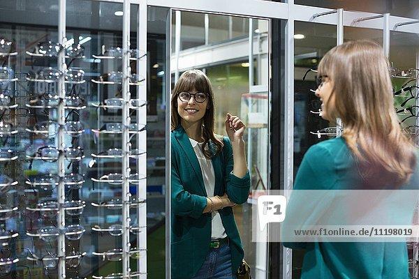 Junge Frau beim Anprobieren einer Brille vor dem Spiegel im Optikgeschäft