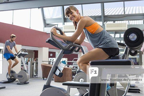 Porträt einer Frau  die in einem Fitnessstudio trainiert  mit einem Mann im Hintergrund.