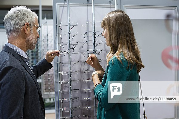 Verkäuferin beim Kunden für Brillen im Optikergeschäft
