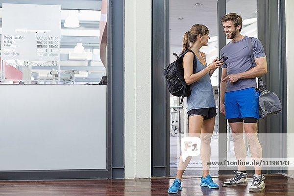 Junges Paar lächelt sich an der Tür eines Fitnessclubs an.