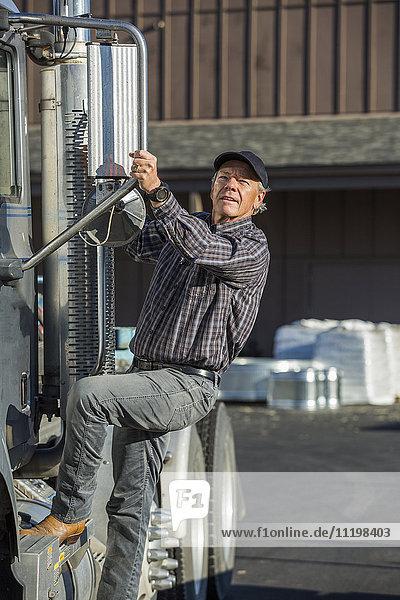 Caucasian man climbing into semi-truck