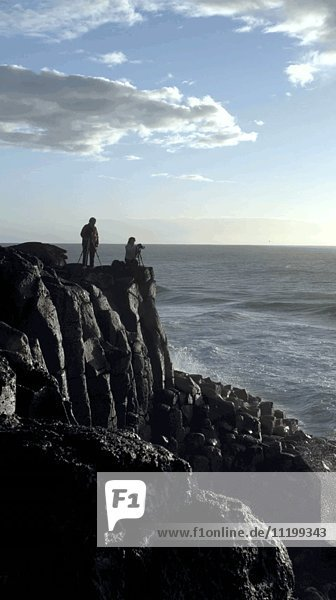 Two People Taking Photos on Ocean Cliff