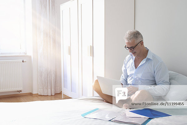Mature businessman using laptop while sitting on bed at home