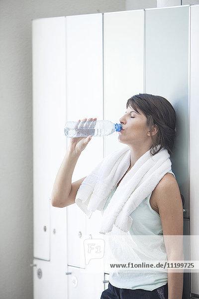 Woman drinking bottled water in locker room